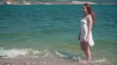 A girl in a white beach dress, walks along the seashore. A beautiful girl with Live Action