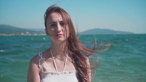 Portrait of a girl in a white dress on the seashore. Beautiful girl, lips with Live Action