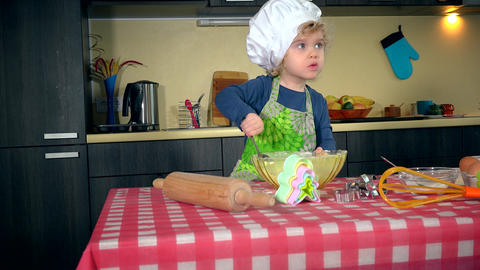 girl mix flour in bowl on table in kitchen. Girl in apron and white chef hat. 4K Live Action