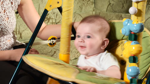 Mom shakes her baby boy on a swing Stock Video Footage
