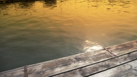 Ripples waves on lake & wood piers,sun light reflection in water in evening Footage