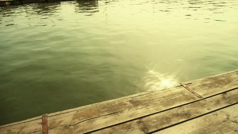 Ripples waves on lake & wood piers,sun light reflection in water Footage