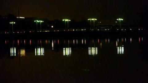 reflection on lake with busy traffic on bridge at night... Stock Video Footage