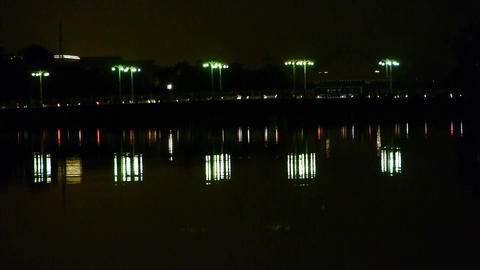 reflection on lake with busy traffic on bridge at night in Beijing China Footage