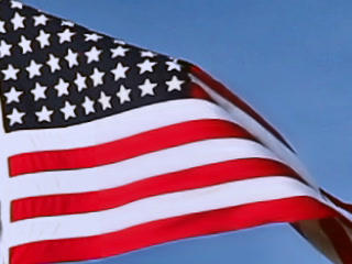 USA flag flying on the wind on blue sky background, closeup view Footage