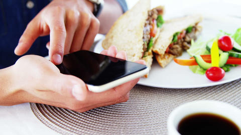 Man in lunch bar with smartphone and coffee Live Action