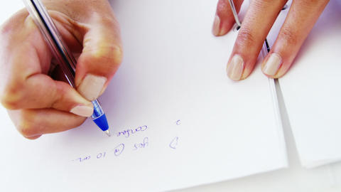 woman taking notes on blank paper Footage