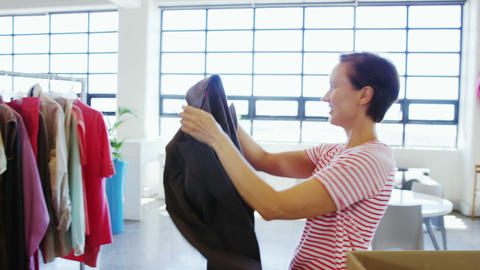 Woman arranging clothes on clothing rack Live Action