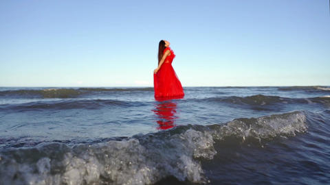 Long haired lady in red dress stands in blue sea water Live Action