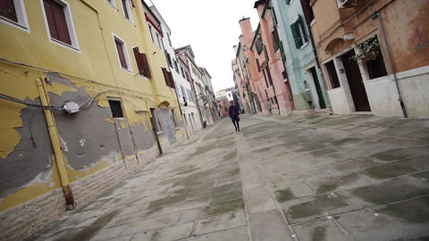 Stylish guy in long dark coat walks along empty old street Live Action