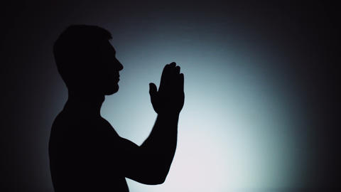 A man prays to God, folding his arms and stretching them up. Emotions, prayer Live Action