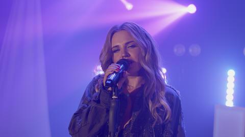 Live vocal performance of emotional singer in denim jacket. Vocalist girl Live Action