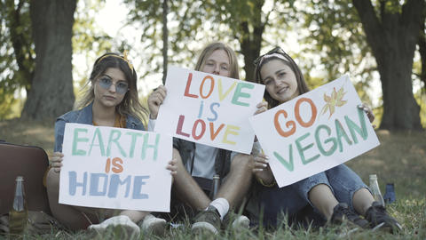 Three young hippies showing posters Earth is home, Love is love, and Go vegan Live Action