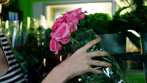 Beautiful female florist smelling bunch of pink rose Footage