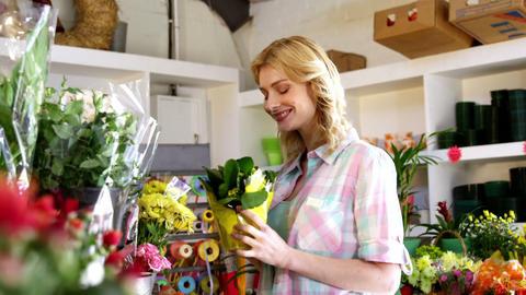 Beautiful female florist smelling flower in flower shop Footage