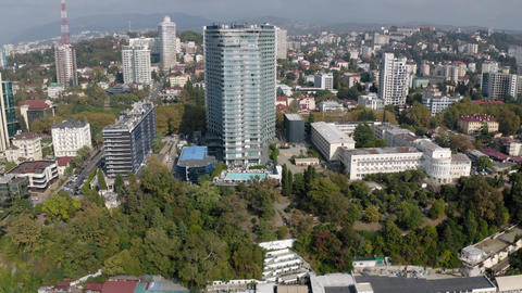 Aerial reverse view city Sochi modern architecture with waterfront at sunny Live Action