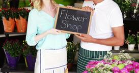 Smiling florists holding flower shop sign on slate in flower shop Footage