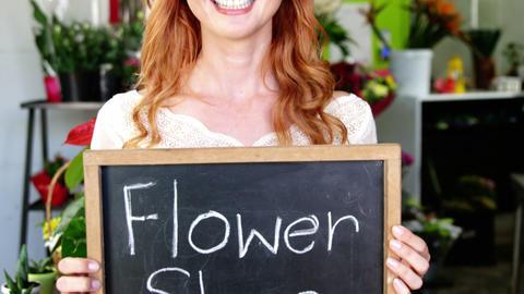 Smiling florist holding flower shop sign on slate Live Action