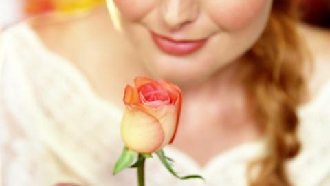 Beautiful female florist smelling rose Footage