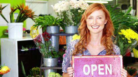 Smiling florist holding open sign on slate in flower shop Footage
