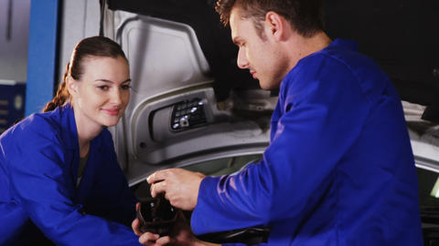 Male mechanic checking a car parts while female mechanic servicing a car Live Action