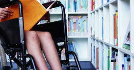 Disabled school girl reading book in library at school Footage