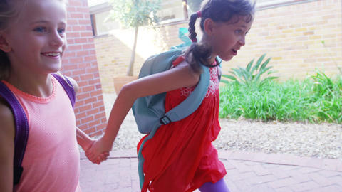 School girl holding hands and running together in corridor at school Footage