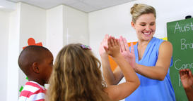 School teacher giving high five to school kids in classroom Live Action