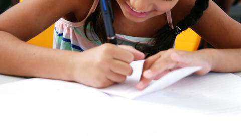 Schoolgirl writing on chit in classroom Live Action