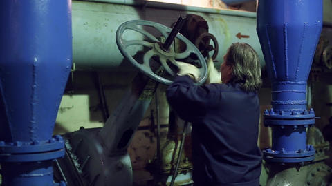 A woman twists the industrial valve Live Action