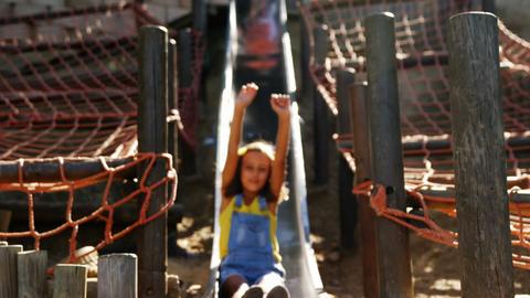 Schoolgirl sliding on slide in school playground Live Action