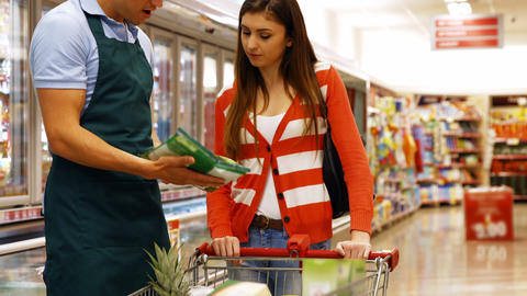Smiling male staff assisting a woman with grocery shopping Live Action
