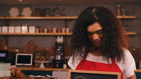 Smiling waitress showing slate with open sign Live Action