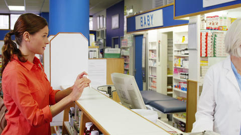 Pharmacist assisting the box of drug to customer Footage