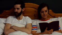 Man getting annoyed while woman reading book on bed Footage