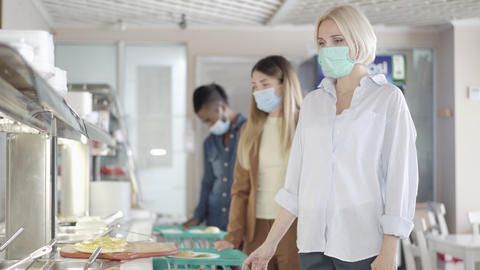 Ill young blond woman in face mask sneezing and queue moving away in lunchroom Live Action