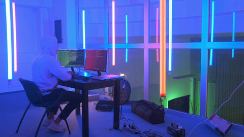 Hacker working place: hacker working in a room with colored neon lights Live Action