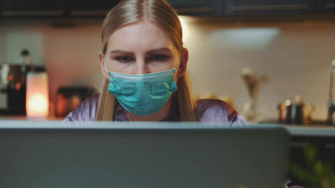 Medium shot of computer monitor and woman in medical mask reading something on Live Action