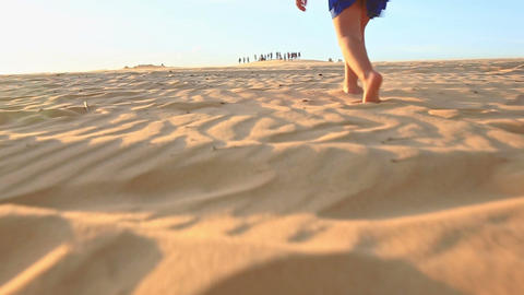 Small Girl Walks Barefooted on Sand Dunes Stops Tired at Sunset Footage