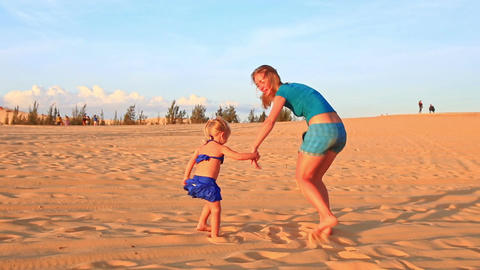 Backside Mother Small Girl Join Hands Run on Dunes at Sunset Live Action