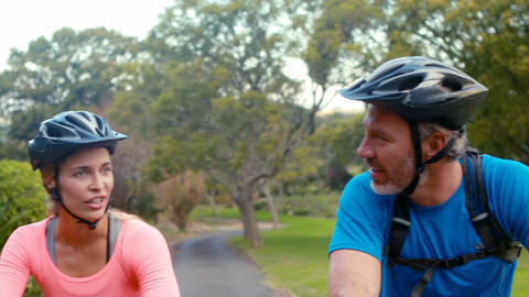 Couple interacting face to face while riding bicycle Footage