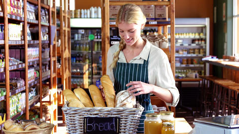 Smiling female staff checking loaf of bread at bread counter Footage