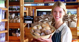 Smiling female staff holding basket of sesame breads at bread counter Live Action