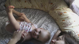 Baby girl with her mother laying on bed Footage