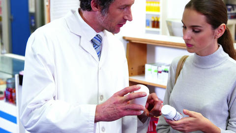 Pharmacist assisting the bottle of drug to customer Live Action