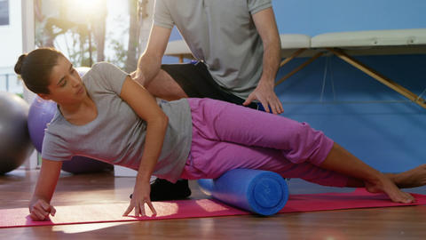Physiotherapist assisting woman while exercising on exercise mat Live Action