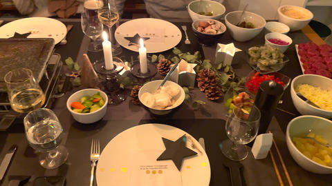 Cozy Raclette dinner with tasty ingredients and candlelight. Christmas decoration with fir cone Live Action