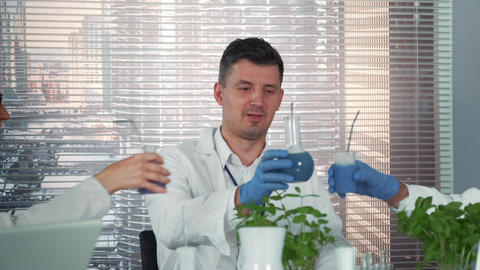 Close-up of cheerful scientist in lab coat making cheers with his colleagues of Live Action