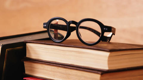 Stack of books with spectacles on a desk Footage