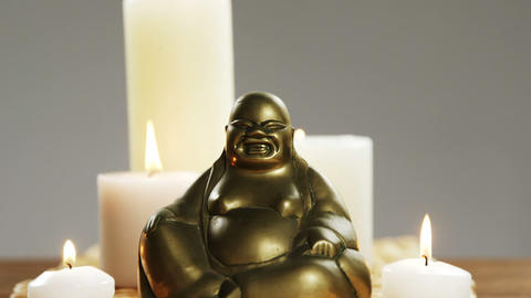 Close-up of laughing buddha figurine with burning candles ビデオ